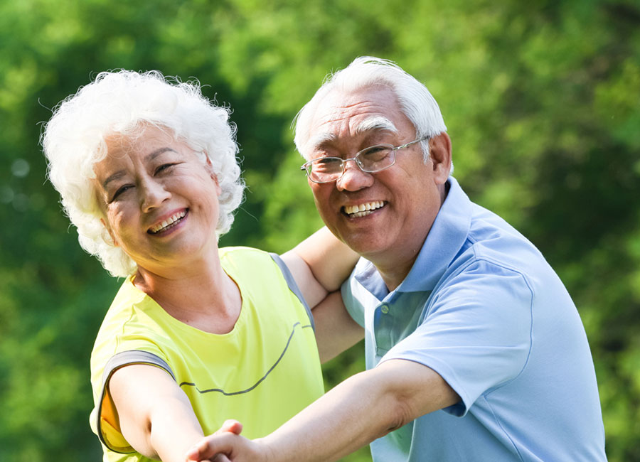 Elderly couple dancing together outdoors